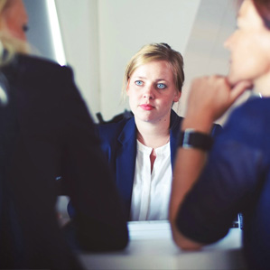 A corporate woman sitting with two others in an HR support role